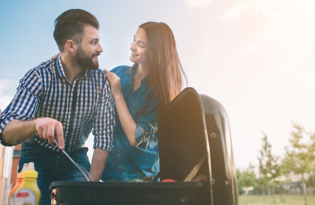 Friends making barbecue and having lunch in the nature. couple having fun while eating and drinking at a pic-nic - happy people at bbq party. Premium Photo