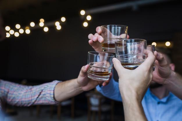 Amici facendo acclamazioni con bicchieri di whisky Foto Gratuite