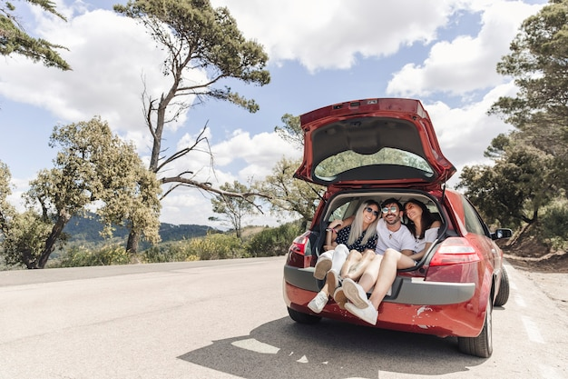 Friends making enjoyment in the car trunk on road Free Photo