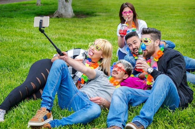Friends making selfie at the summer festival with masks and necklaces Premium Photo