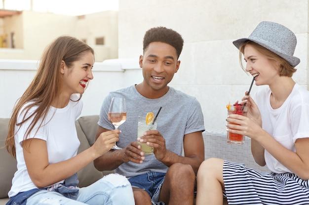 Друзья встречаются вместе, пьют белое вино и свежие коктейли, обсуждая что-то Бесплатные Фотографии