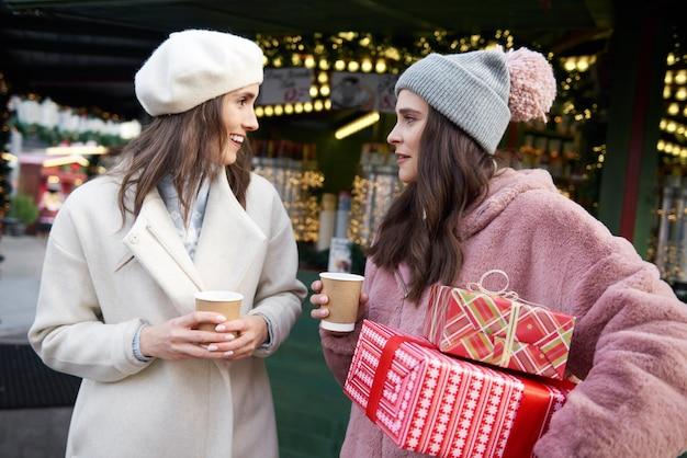 プレゼントを運んだり、グリューワインを飲んだりするクリスマスマーケットの友達 無料写真
