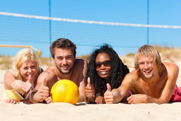 Friends playing beach volleyball Premium Photo