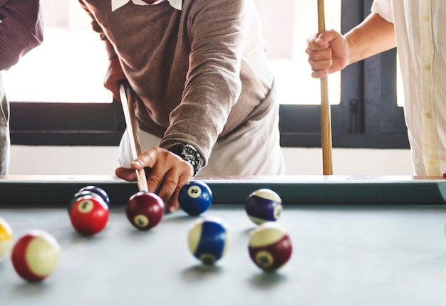Friends playing pool game together Free Photo