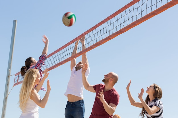 Friends playing volleyball at beach Photo | Premium Download