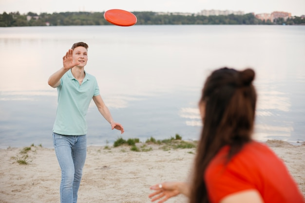 Friends playing with frisbee on the beach Free Photo