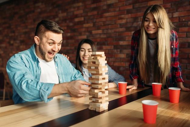 Друзья играют в настольную игру, выборочный фокус на башне Premium Фотографии