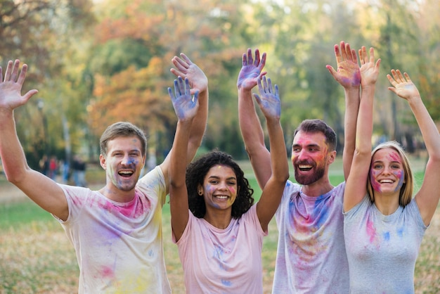 Friends posing while holding colored hands in the air Free Photo