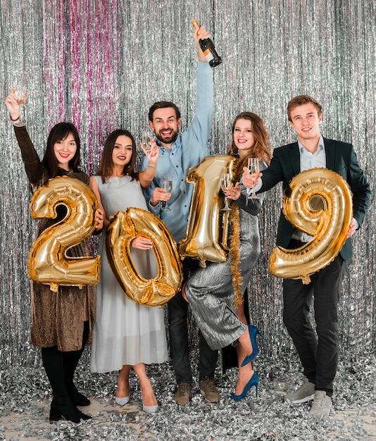 Friends posing with golden balloons new year party Free Photo