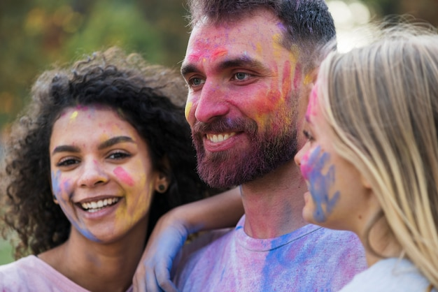 Friends posing with painted faces at festival Free Photo