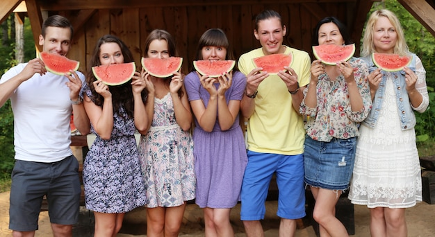 Friends posing with watermelon slices Free Photo