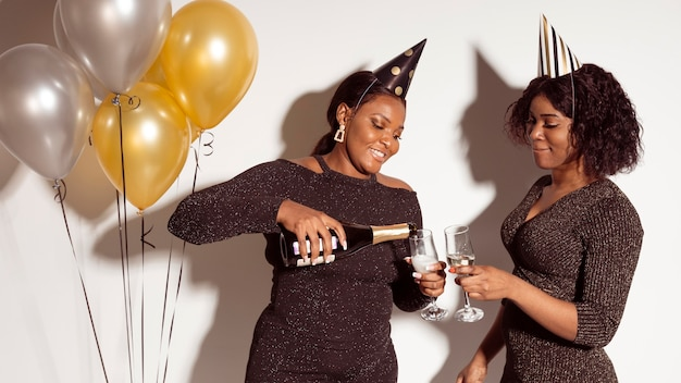 Amici versando bicchieri di champagne festa di buon compleanno Foto Gratuite