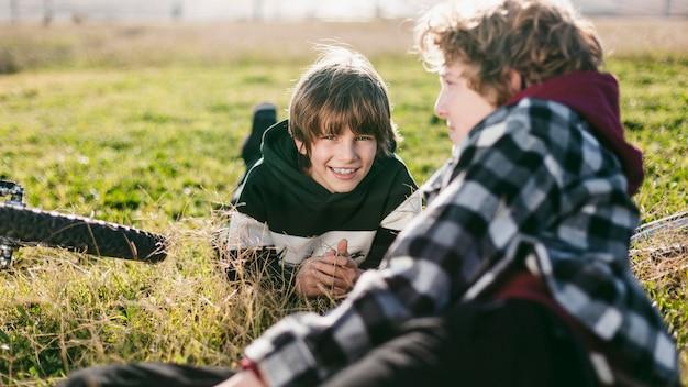 自転車に乗っている間、芝生で休んでいる友達 無料写真