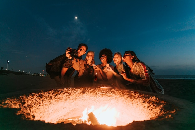 Friends roasting marshmallows for s'mores Premium Photo