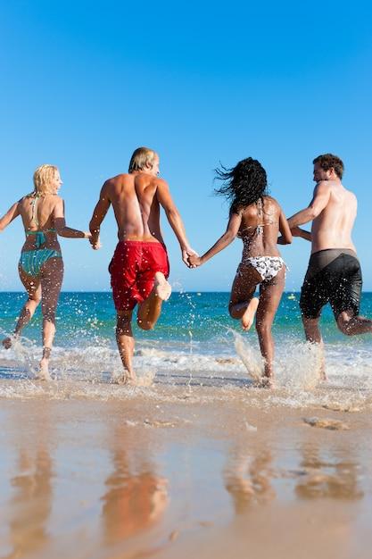 Friends running on beach vacation Premium Photo