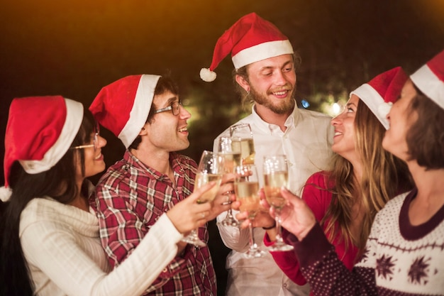 Friends in santa hats clinking glasses at party Free Photo
