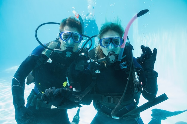 Friends on scuba training submerged in swimming pool looking to camera Premium Photo