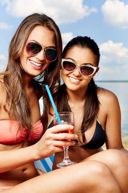 Friends sharing a drink on the beach Free Photo