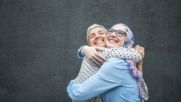 Friends sharing a hug with black background Free Photo
