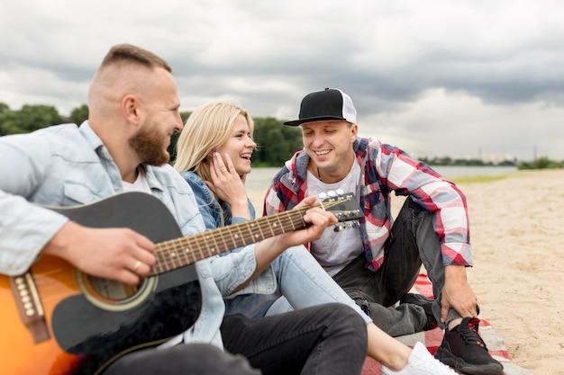 Друзья поют и играют на гитаре на пляже Бесплатные Фотографии