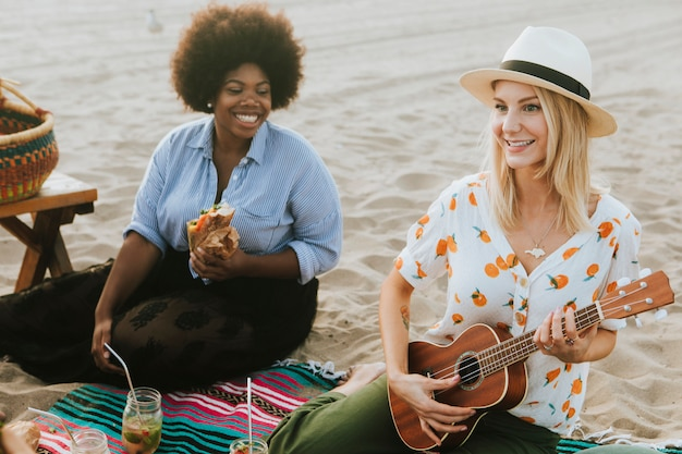 Friends singing together at a beach picnic Premium Photo