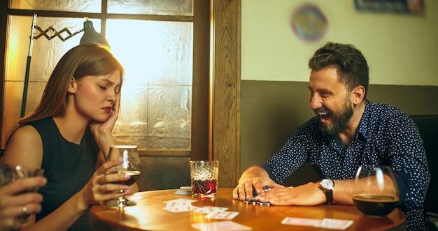 Друзья сидят за деревянным столом. друзья веселятся во время игры в настольную игру Бесплатные Фотографии