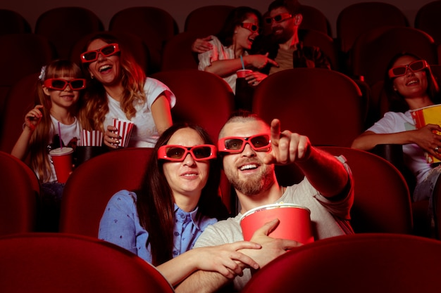 Friends sitting in cinema watch film eating popcorn and drinking water. Premium Photo