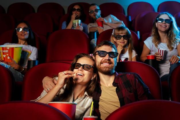 Friends sitting in cinema watch film eating popcorn and drinking water. Premium Photo