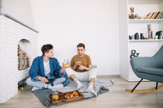 Friends sitting on floor having delicious food at home Free Photo
