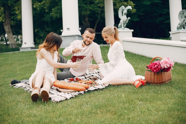 Friends sitting in a garden on a picnic Free Photo