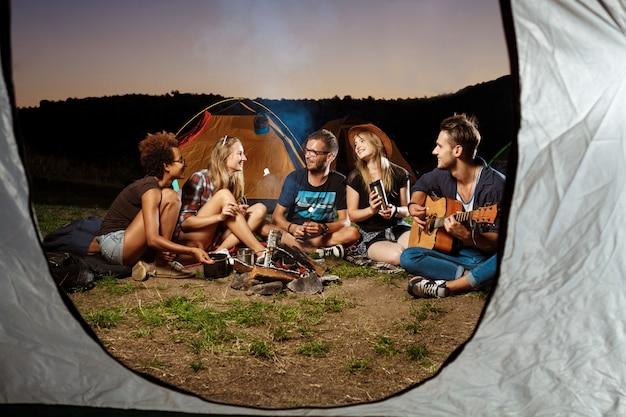 たき火のそばに座って、笑って、ギターを弾いて友達キャンプグリルマシュマロ。 無料写真