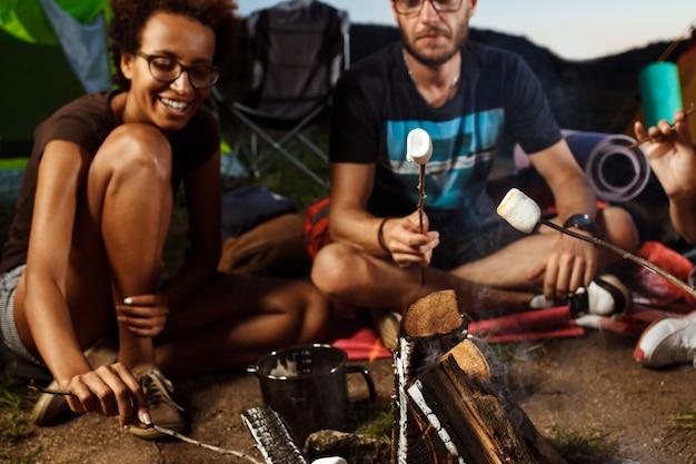 Друзья сидят возле костра, улыбаются, играют на гитаре Бесплатные Фотографии