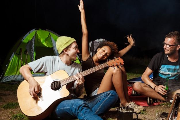 Друзья сидят возле костра, улыбаются, говорят, отдыхают, играют на гитаре Бесплатные Фотографии