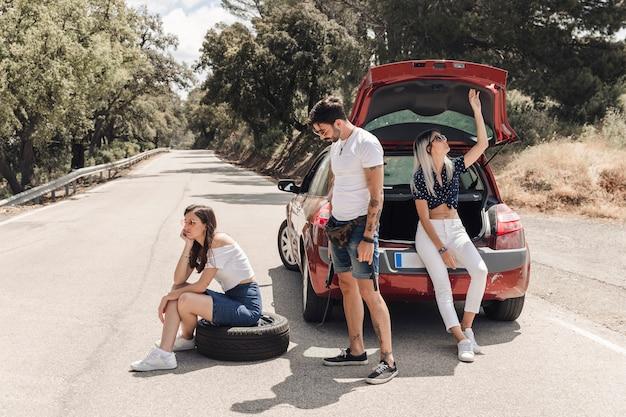 Friends sitting near the breakdown car on road Free Photo