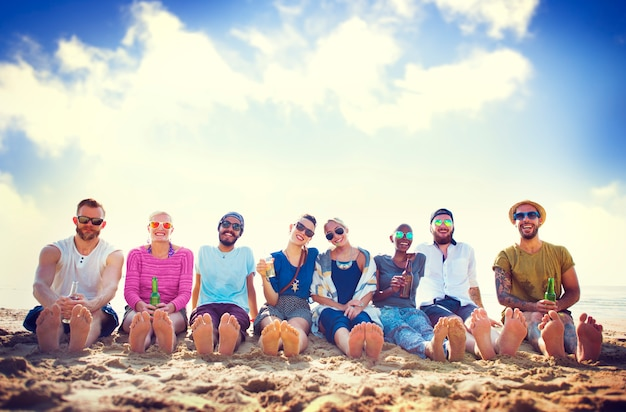 Friends sitting in the sand on a beach Premium Photo