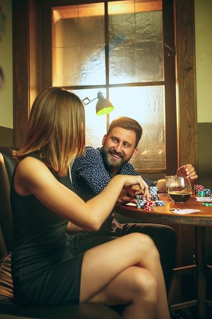 Amici seduti al tavolo di legno. amici che si divertono durante il gioco da tavolo. Foto Gratuite