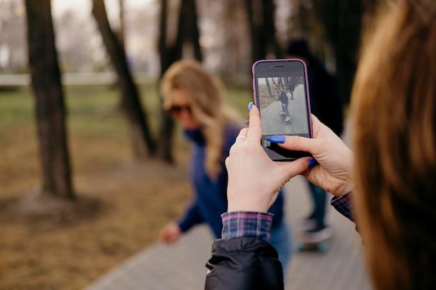 女性が写真を撮っている間、友達が公園でスケートボードをしている 無料写真
