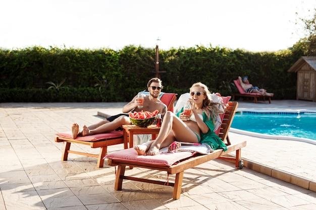 Amici che sorridono, bevendo cocktail, sdraiati su sedie a sdraio vicino alla piscina Foto Gratuite