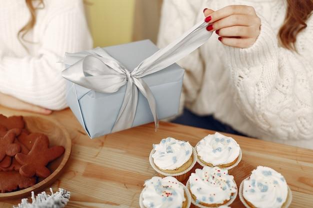 친구들은 집에서 시간을 보냈습니다. 크리스마스 선물을 가진 두 여자입니다. 산타의 모자에있는 여자. 무료 사진