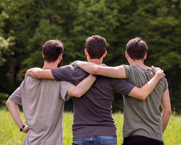 Friends standing on glade with hands on each other shoulders Free Photo