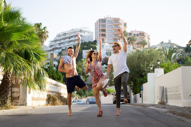 Friends on summer vacation, laughing, having fun, jumping, walking through the streets of the city. Free Photo