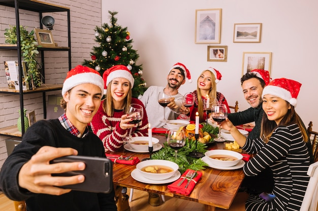 Friends taking selfie at christmas dinner Free Photo