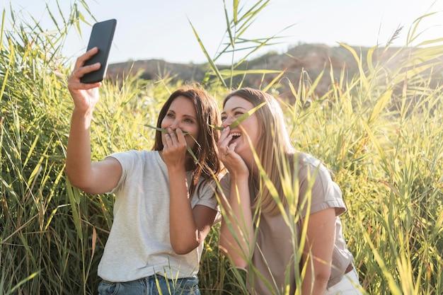 Amici che scattano un selfie mentre viaggiano in un luogo selvaggio Foto Gratuite