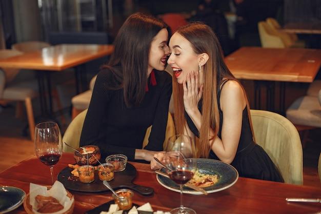 친구 이야기와 디너 파티에서 재미. 저녁 식사를하는 사람들의 우아하게 옷을 입은 여성. 무료 사진