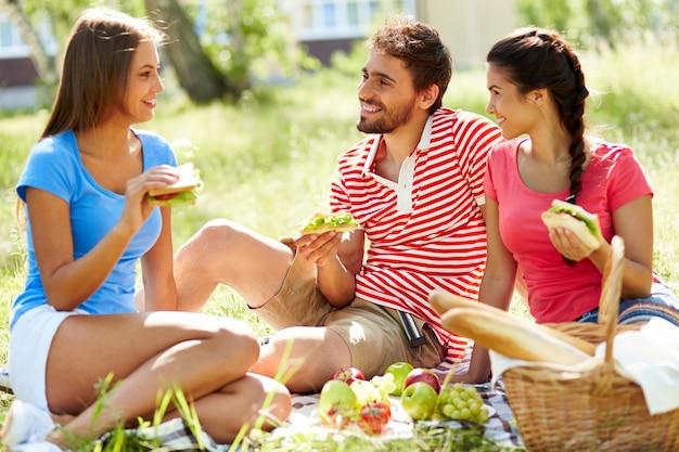 Amici a parlare e mangiare nel parco Foto Gratuite