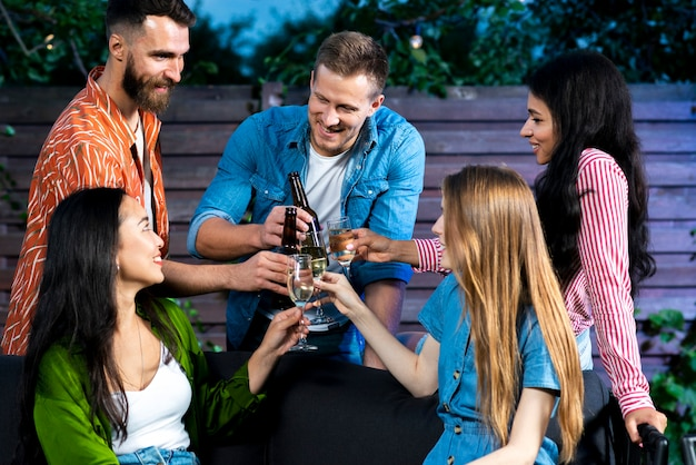 Friends toasting drinks together outdoors Free Photo