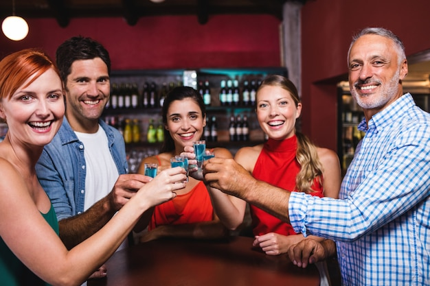 Friends toasting tequila glasses in nightclub Premium Photo