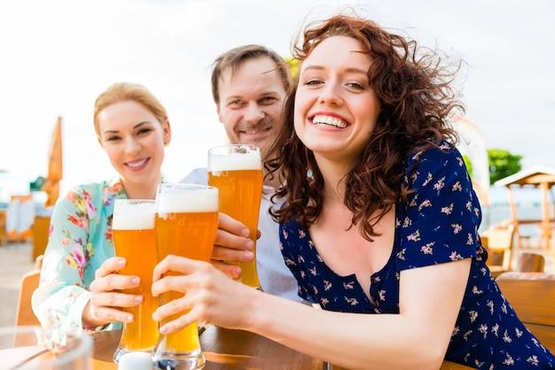 Friends toasting with beer in garden restaurant Premium Photo