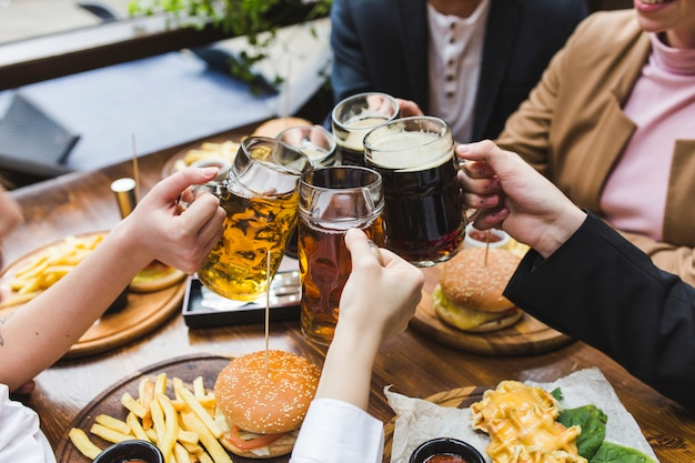 Friends toasting with beer in restaurant Free Photo