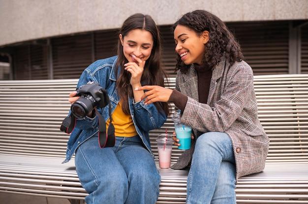 Друзья вместе на открытом воздухе с камерой и молочным коктейлем Бесплатные Фотографии
